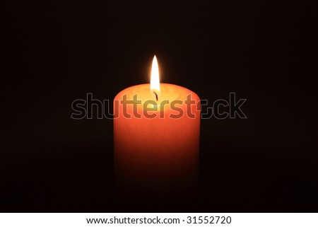 A candle glowing in the dark
