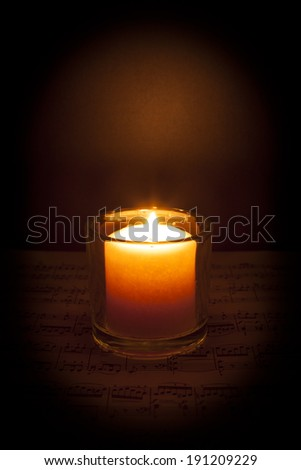A candle glows in the darkness on top of sheet music; dark vignette - stock photo
