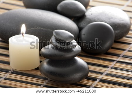 A candle next to a tower of zen stones, time to relax - stock photo