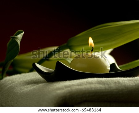 A candle on a towel at spa - stock photo