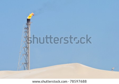 A candle tower burning off excess gas at an oil refinery in the desert. - stock photo