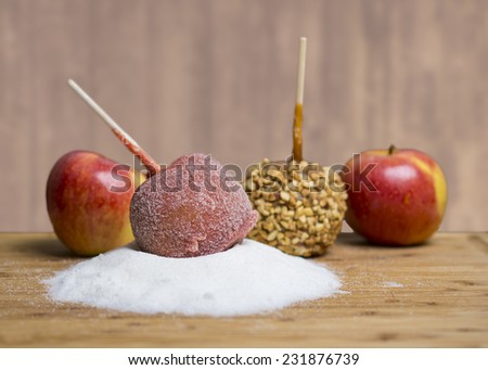 A candy apple coated sugar sits atop a pile of sugar. Another candy apple with chopped nuts behind it, with two Gala apples. On a wooden cutting board with a textured background. - stock photo
