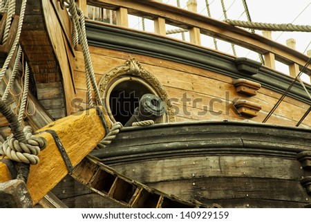 A cannon coming out of a hole in an old galeon - stock photo