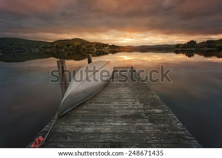 a canoe on a wooden dock on a lake during sunset - stock photo