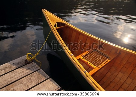 A canoe tied up to a dock. - stock photo
