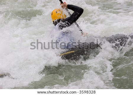 A canoeist in paddling through white water