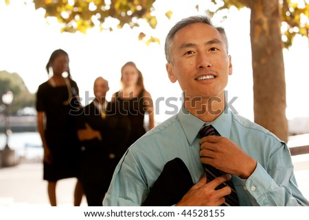 A cansual asian business man adjusting his tie - stock photo