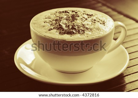 A cappuccino coffee on a saucer in sepia tone.