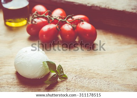 A caprese salad making ingredients close up. Red tomatoes, mozzarella, extra virgin olive oil and basilicum lying on a wooden background, retro filtered.  - stock photo