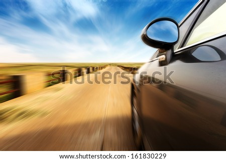 A car at high speed on the road in the countryside - stock photo