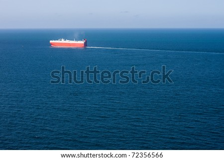 A car carrier cargo ship sails a deep blue vast ocean, leaving a think wake behind.  Horizontal image with deep vessel. - stock photo