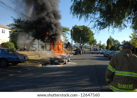 A car caught on fire in the street and firefighters work on putting out the fire. - stock photo