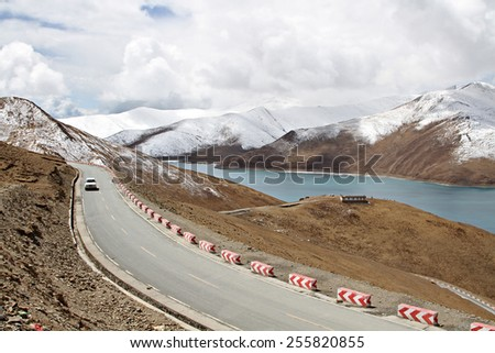 A car drives along the Friendship Highway past Yamdrok Lake in rural Tibet. - stock photo
