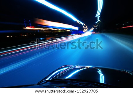 A car driving on a motorway at high speeds, overtaking other cars