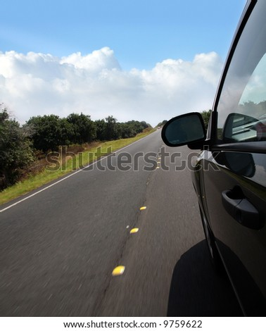 A car driving on the road in the countryside - stock photo