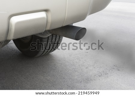 A car emits carbon monoxide gas from its exhaust tailpipe, showing how pollution is formed. - stock photo