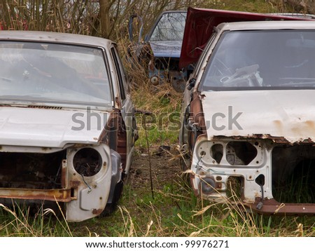 A car graveyard with old and rusted car wrecks - stock photo