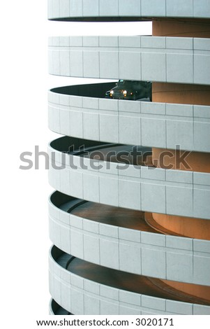 A car heads down the long spiral of a parking garage ramp. White background. - stock photo
