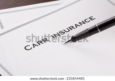 A car insurance policy with a pen ready for signing. - stock photo