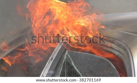 A car is burning after an accident, crash, no one was hurt, firefighters are on the way - stock photo