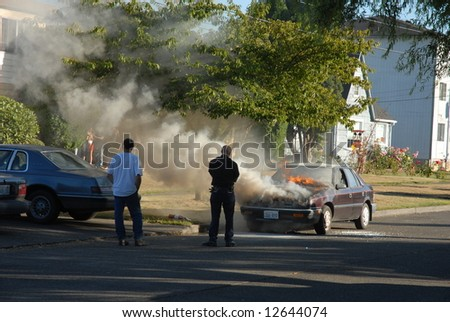 A car is burning on the street. The story of a firefighter putting out the fire.