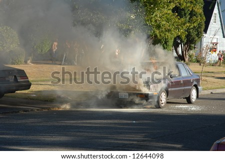 A car is burning on the street. The story of a firefighter putting out the fire. - stock photo