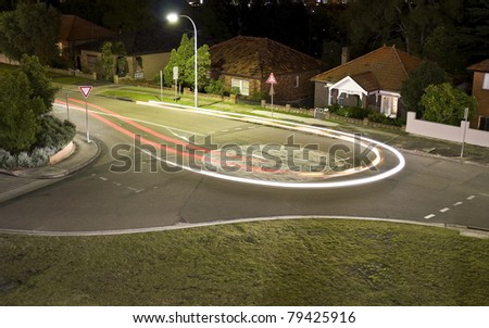 A car makes a U-turn in a round-about in a suburban built-up area, creating a light trail - stock photo