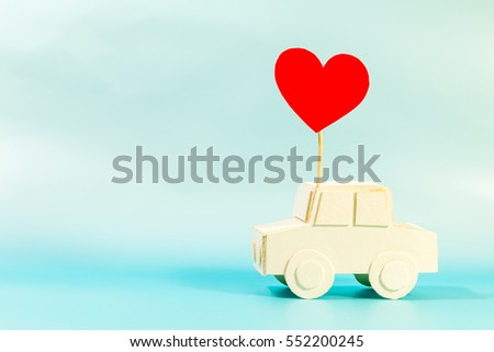 A car model and red heart on blue background.