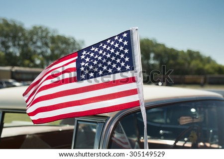 A car mounted American flag blowing in the wind. - stock photo
