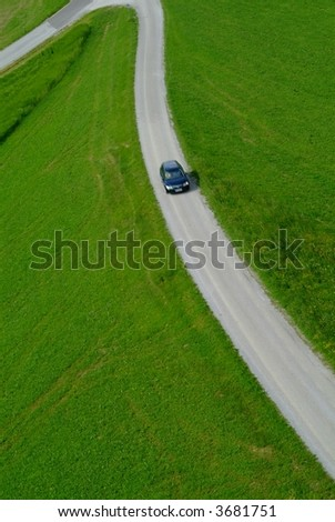a car on a road crossing the green meadow