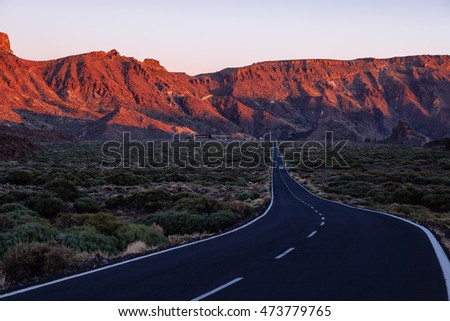 A car on the road on El Teide, the tall volcano on Tenerife island, with a classical vanishing point and the beautiful sunset warm light on the rocky mountains
