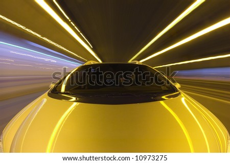 A car, seen from the front racing at high speeds along a straight motorway - stock photo