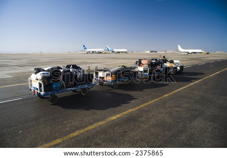 a car takes away luggage of the air passengers to the plane - stock photo