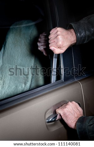 A car thief uses a Slim Jim tool to pop the lock on a car door to steal it. - stock photo