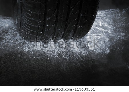 A Car tire on a wet road. The rain groove is a design element of the tread pattern specifically arranged to channel water away from the footprint. - stock photo