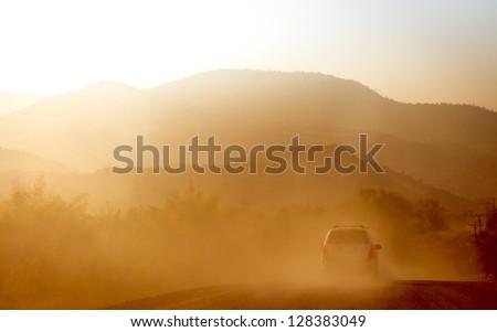 A car traveling through stormy desert - stock photo