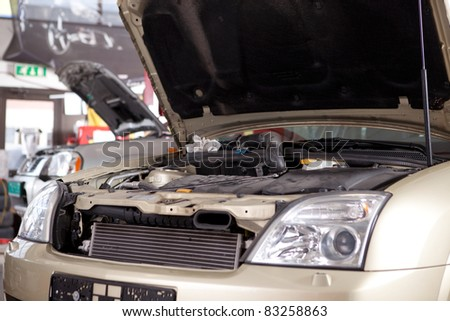 A car with a hood up in a professional auto repair shop - stock photo