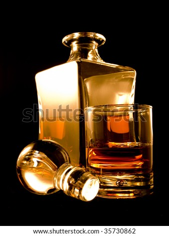 A carafe filled with brandy on a black background - stock photo