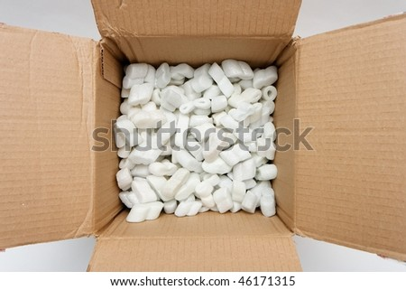 A cardboard box with packing foam pellets top view - stock photo