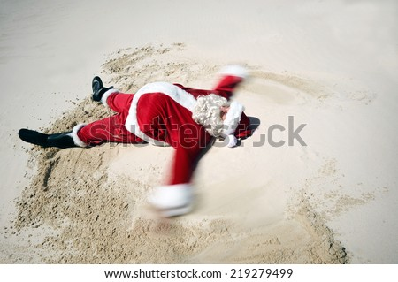 A carefree Father Christmas doing a sand angel on the beach sand with copyspace - stock photo