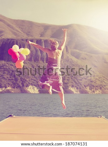 a carefree young woman jumping on a dock with balloons done with a retro vintage instagram filter  - stock photo