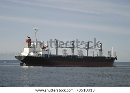 A cargo freighter at anchor in the Seattle harbor with the Olympic Mountains in the background. This container ship has multiple masts. - stock photo