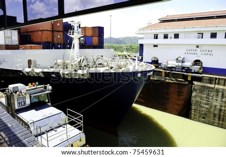 A cargo ship being pulled by mules through the Gatun Locks on the Panama Canal - stock photo