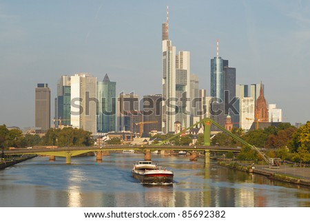 A cargo ship on the Main River and Frankfurt's Skyline n the background. Frankfurt is the financial center of Germany. All major German banks are headquartered in the city.