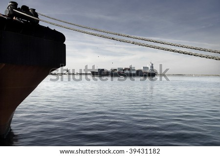 A cargo vessel at the entrance of an harbor. - stock photo