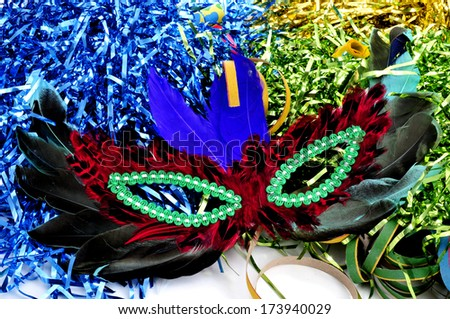 a carnival mask with feathers of different colors on a background with tinsel of different colors - stock photo
