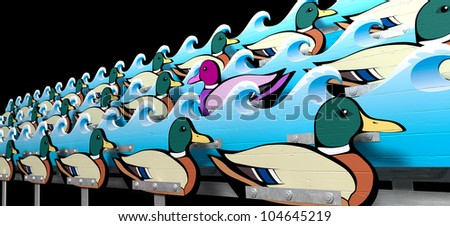 A carnival shooting alley mechanism with a wooden purple toned mallard duck swimming against the flow of the other ordinary mallard ducks in between wave cutouts - stock photo