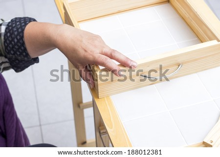 A carpenter builds a small white table