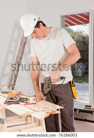 A carpenter drilling with a hand drill in a plank of wood