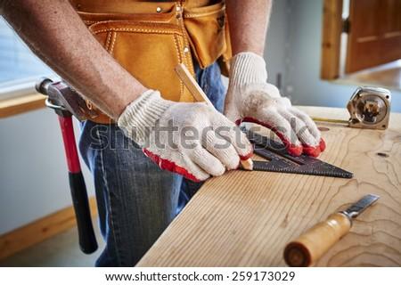 a carpenter making a measurement  - stock photo